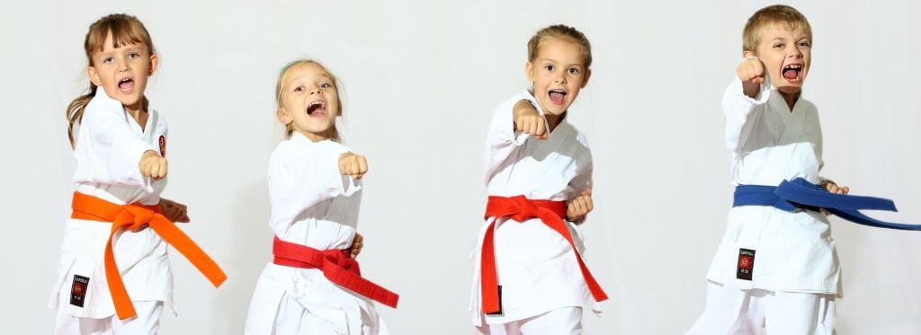 four kids in a line doing karate poses active play