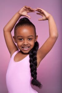Portrait of a cute little African American girl dancing active play