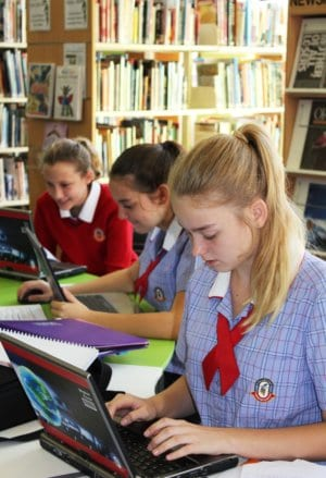 image of three school girls studying in a library.