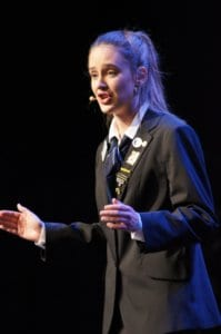 Rebecca Marshall finals debating; a girl with ponytail on stage using microphone and talking