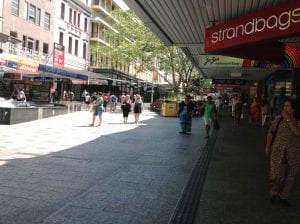 image in queen street mall, in front of standbags. many people walking around.