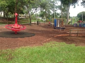 ferny grove playground with spinning apparatus and small climbing walls. Fenced off areas for young children.