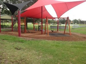 playground in mitchelton covered by mesh share with swingset nd othr paly equipment. Nearby football field.