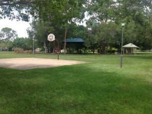 nudgee basketball court with seating area and playground in background