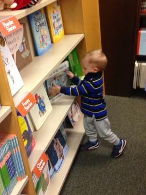 young toddler browsing books in a library