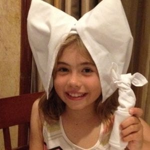 young girl with napkin on her head