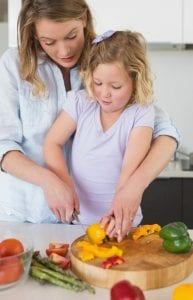 Child learning to chop vegetables, capsicum, from mother