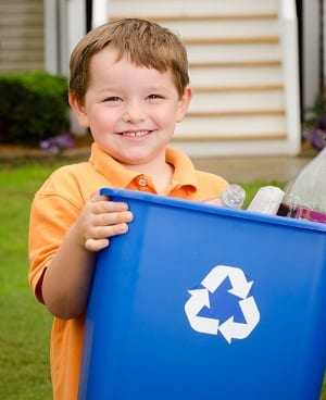 young boy holding bin with recycle symbol on front