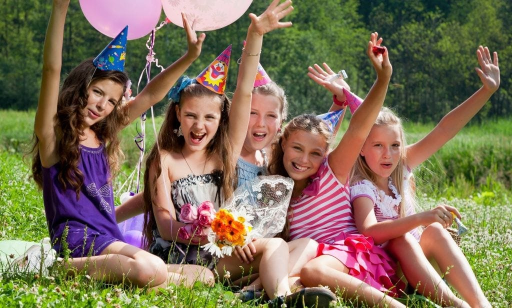 group of girls with hands in air and wearing party hats