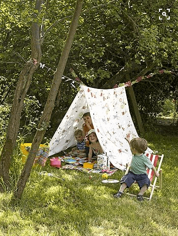 kids in backyard in a simple tent made form rope and a bed sheet