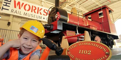 Ipswich to Toowoomba - train rail workshop kid in hardhat smiling in front of train - School holiday activities