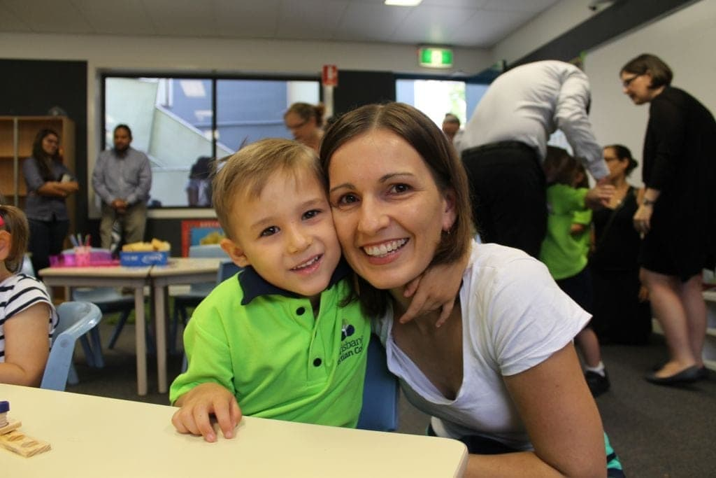 mother and son in school, boy wearing uniform and both smiling