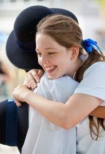 two school girls hugging in uniform