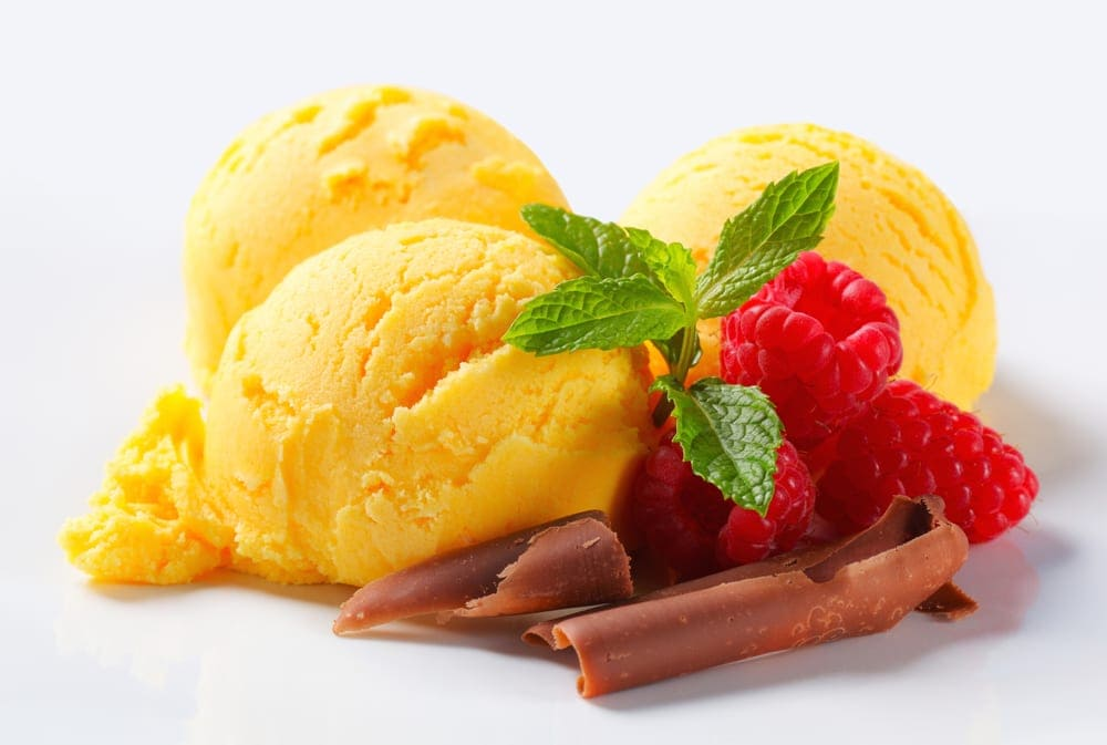 Three scoops of pumpkin ice cream with raspberries and chocolate curls