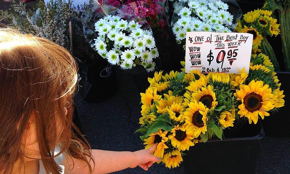 girl points at fresh flowers at Bundall Farmer's Market for Kids