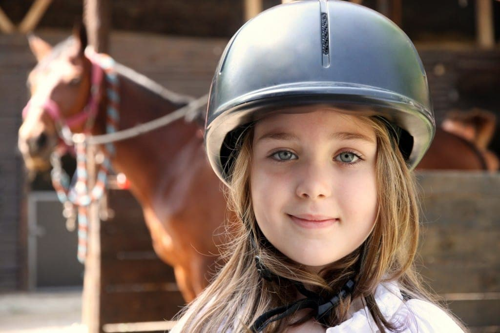 young girl in foreground with blurry horse in the background