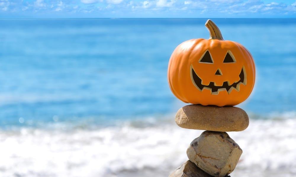 Halloween pumpkin on the beach by ocean