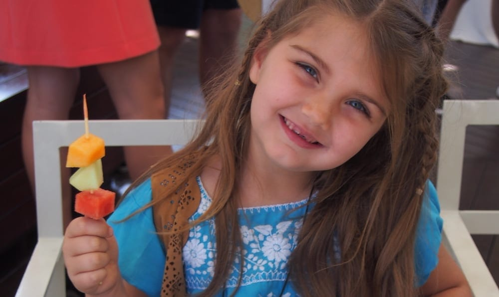 Small smiling child with fruit - Surfers Paradise Kids Week
