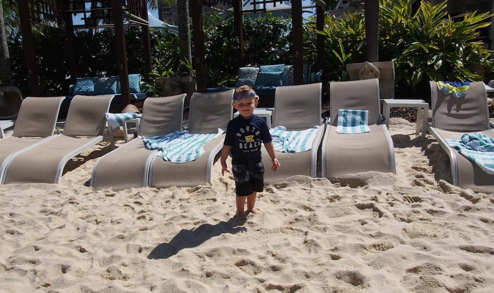 Small Boy standing in front of deck chairs at Marriott Pool - Surfers Paradise Kids Week
