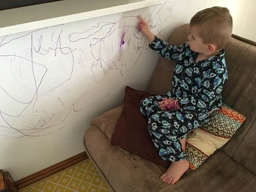 toddler pointing to permanent pen marking on wall