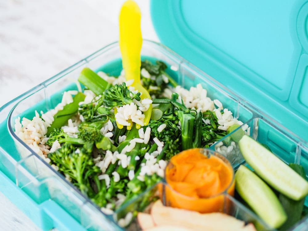 Lunchbox Inspiration of brocollini salad and rice with dip in a lunch box
