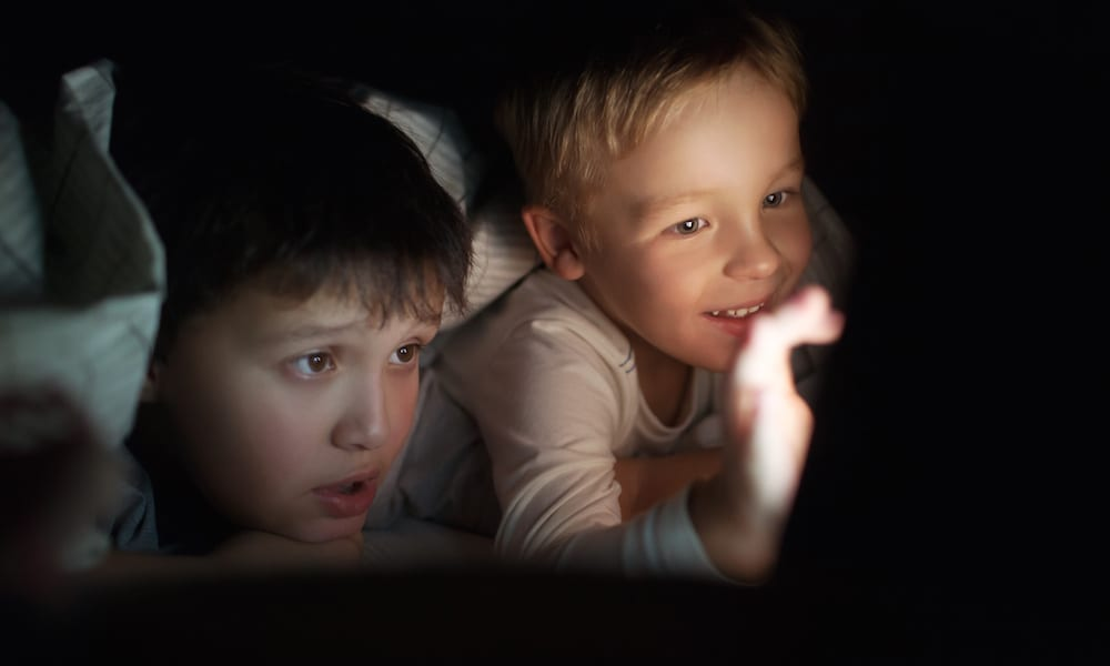 Christmas Holiday activities Two boys lying on bed under blanket at night. They watching movie or cartoon on pad. Screen enlighting their faces in darkness