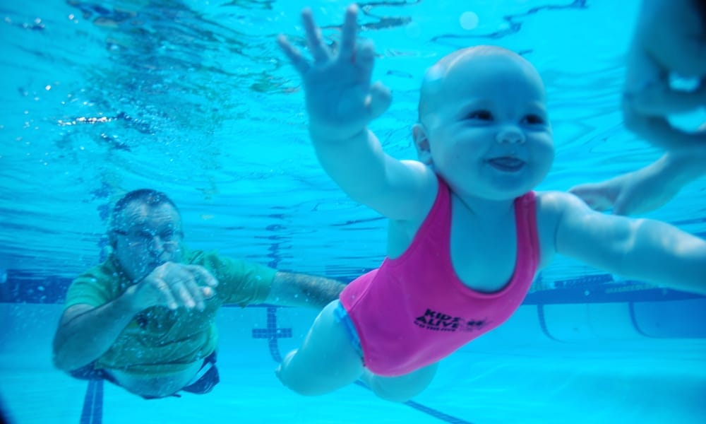 Laurie Lawrence and child in pool
