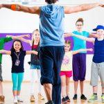 Dance Classes Gold Coast - Dance teacher giving children Zumba fitness class in gym