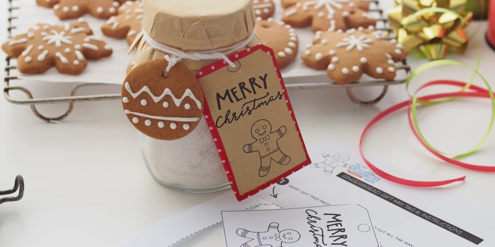 Gingerbread Cookie Mix Christmas Gift Jar in foreground with printed label and cooked gingerbreads in background