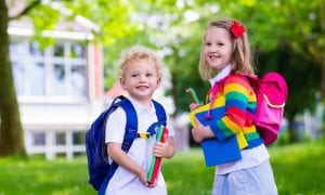 best lunch boxes Child going to school. Boy and girl holding books and pencils on the first school day. Little students excited to be back to school. Beginning of class after vacation. Kids eating apple in school yard