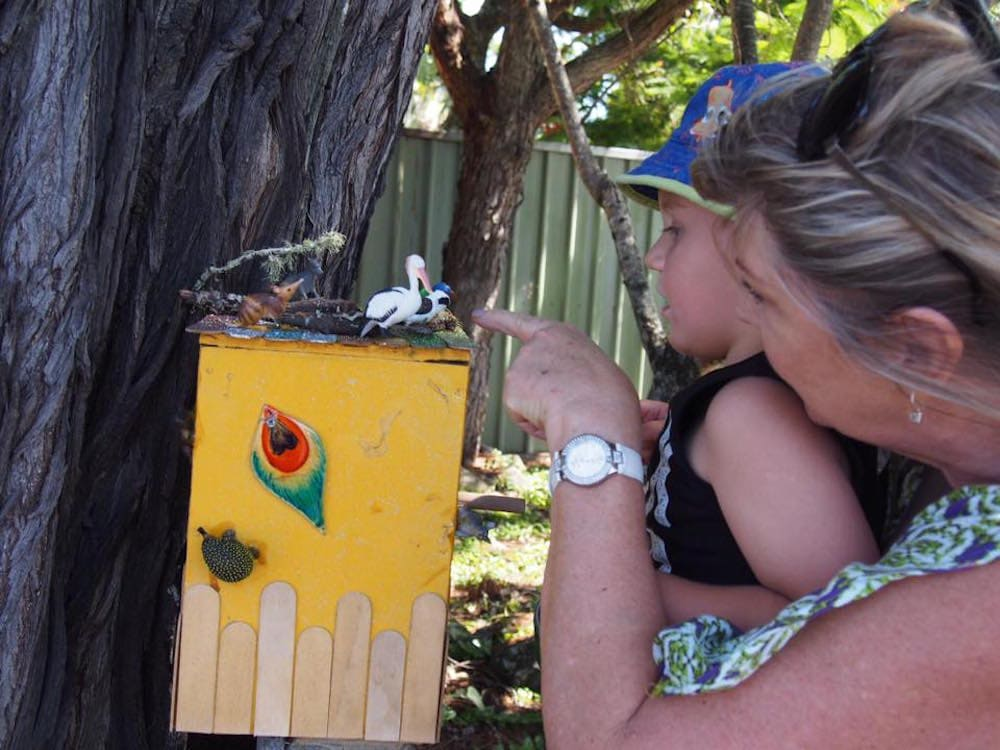 Little boy and grandmother peeping into fairy house in a tree