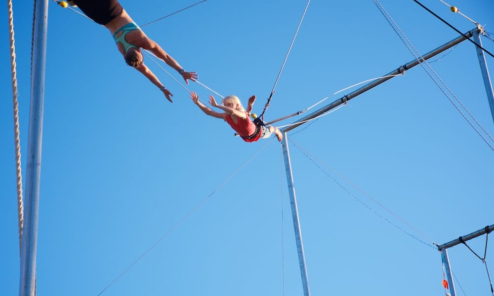 Circus Arts Trapeze young girl reaching out to be caught by instructor while swinging on trapze