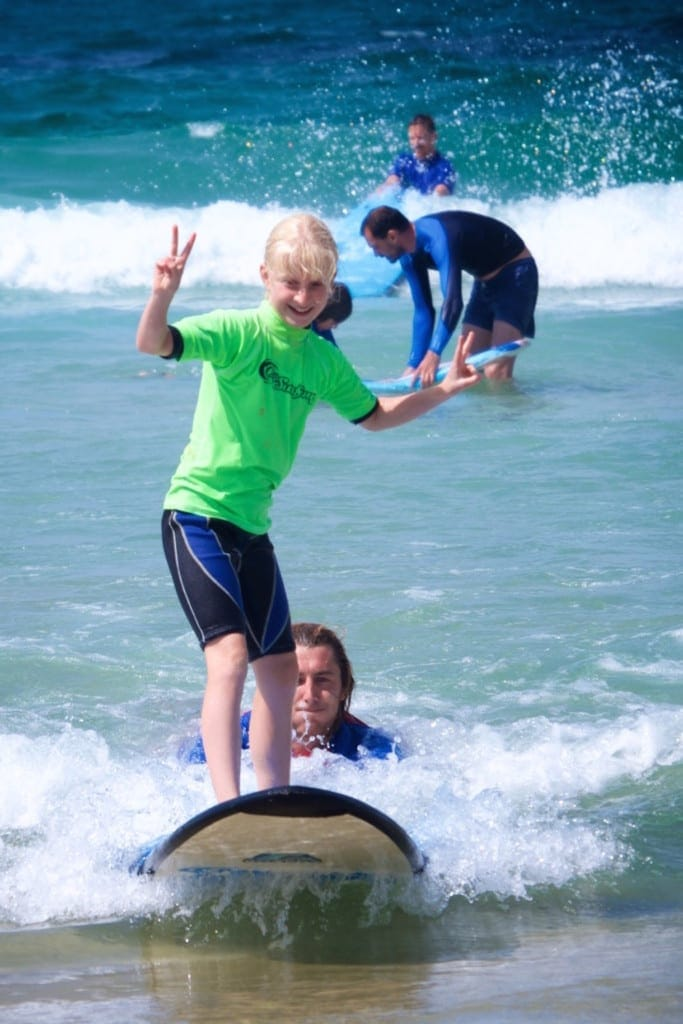 Family Surfing Lessons little girl catching wave into shore with help from an instructor