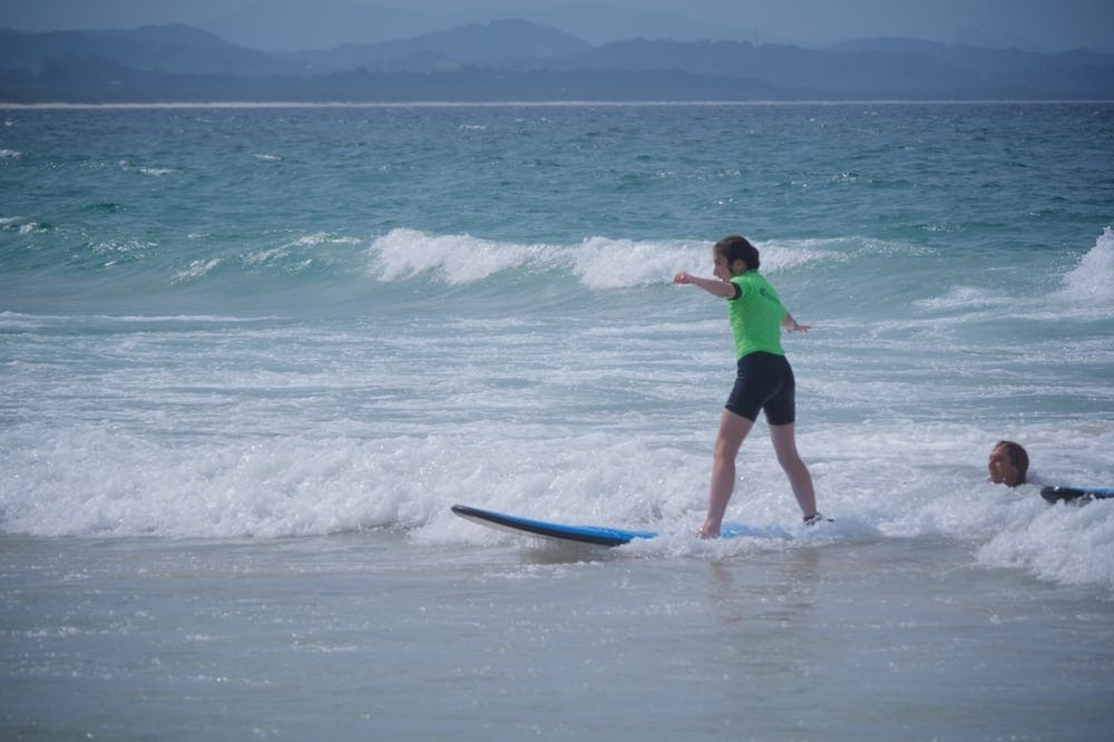 Family Surfing Lessons Young girl catches wave into shore on sunny day