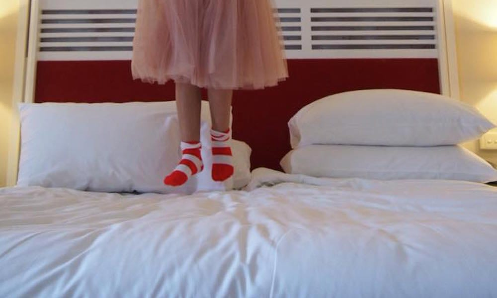 Surfers Paradise Marriott Resort & Spa - little girl in stripey socks jumping on big fluffy bed