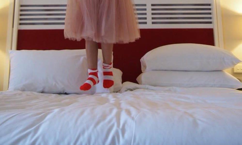 Surfers Paradise Marriott Resort & Spa - little girl in stripey socks jumping on big fluffy bed