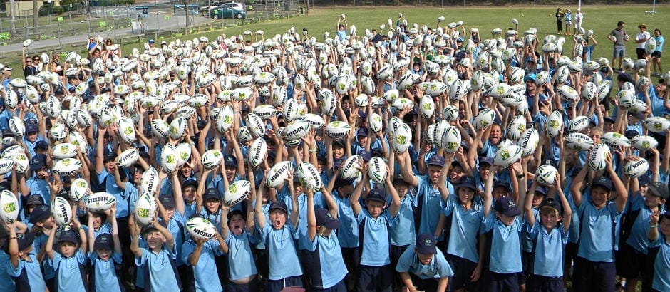 Marymount Catholic Primary School many students in uniform holding balls above their heads