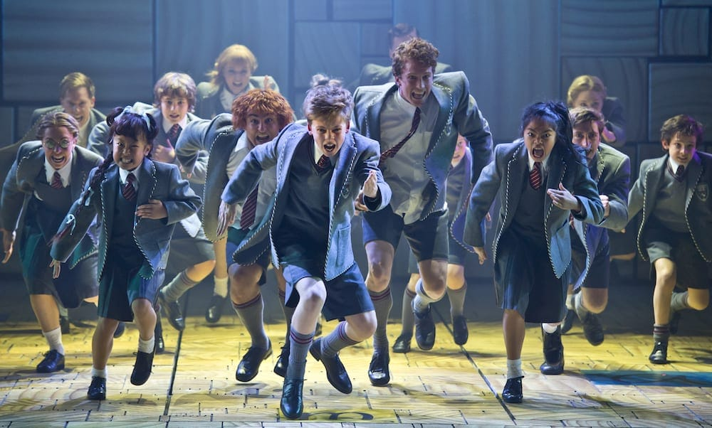 Cast of Matilda The Musical performing on stage