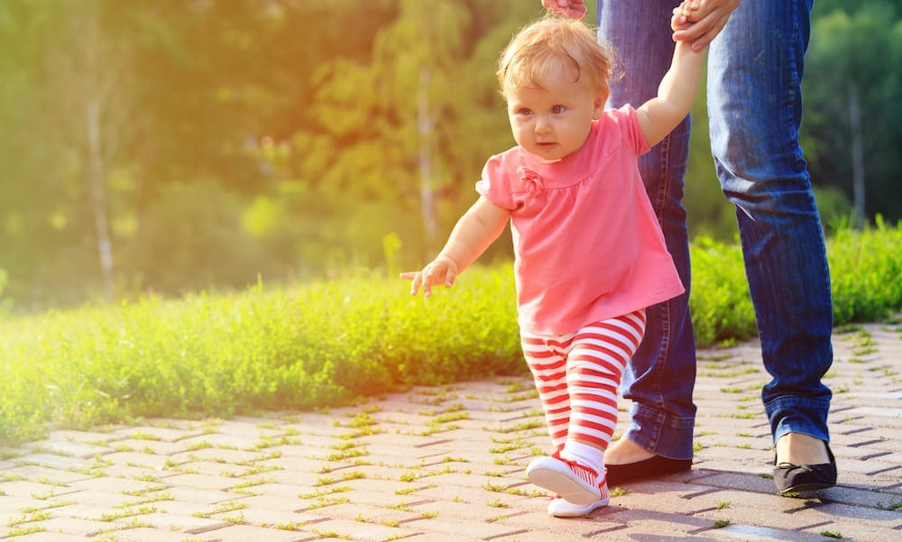 introducing new partner first steps of little girl with mother outdoors, kids learning