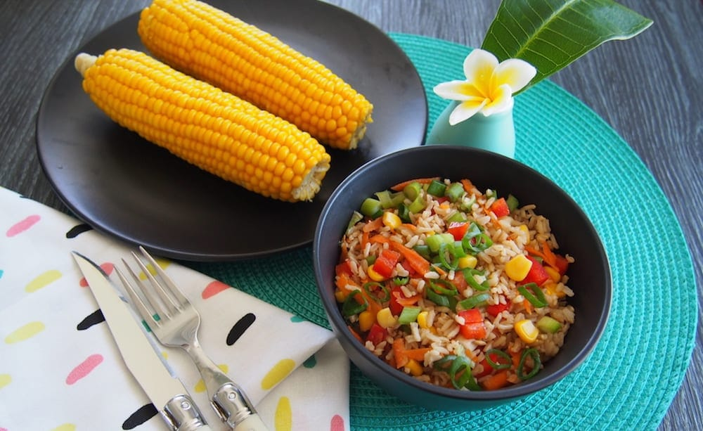 best rice salad black bowl with rice salad next to black plate with two corn kernels, and by a vase featuring one frangipani flower and leaf
