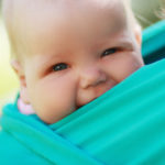 Baby wearing Smiling baby close to mum in sling outdoor