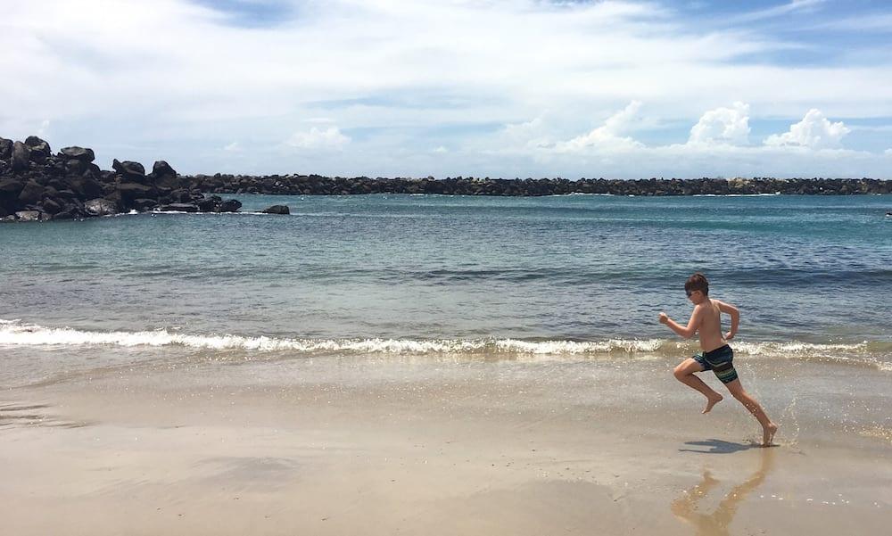 tryathlon kid running along beach in training for tryathlon