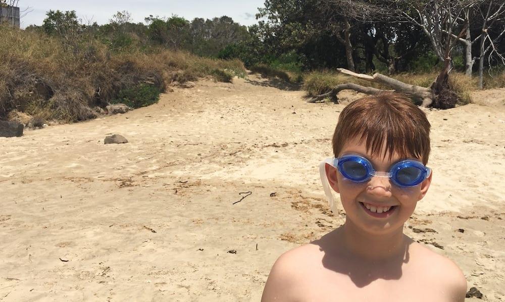 tryathlon kid wearing goggles on beach
