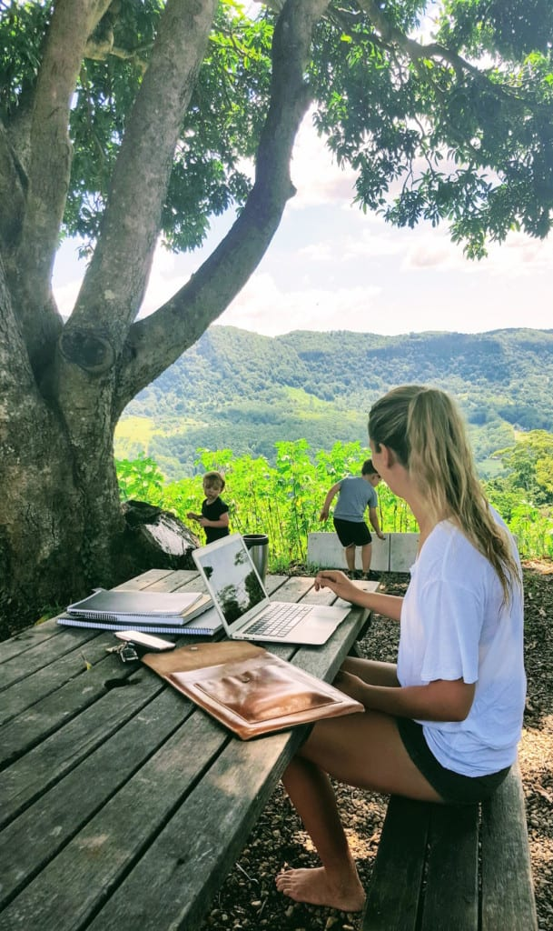 Freeman's Organic Farm mum working on laptop outdoors while children play happily