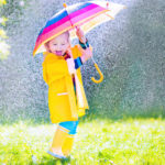 rainy day activities Funny cute curly toddler girl wearing yellow waterproof coat and boots holding colorful umbrella playing in the garden by rain and sun weather on a warm autumn or sumemr day