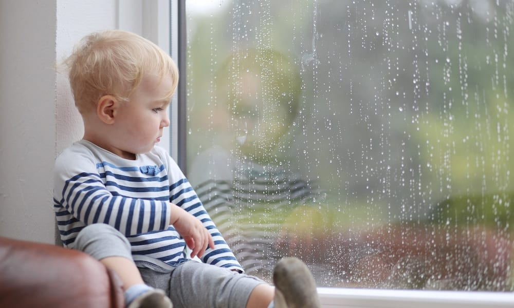 rainy day activities Cute baby girl looking outside through the window during rain