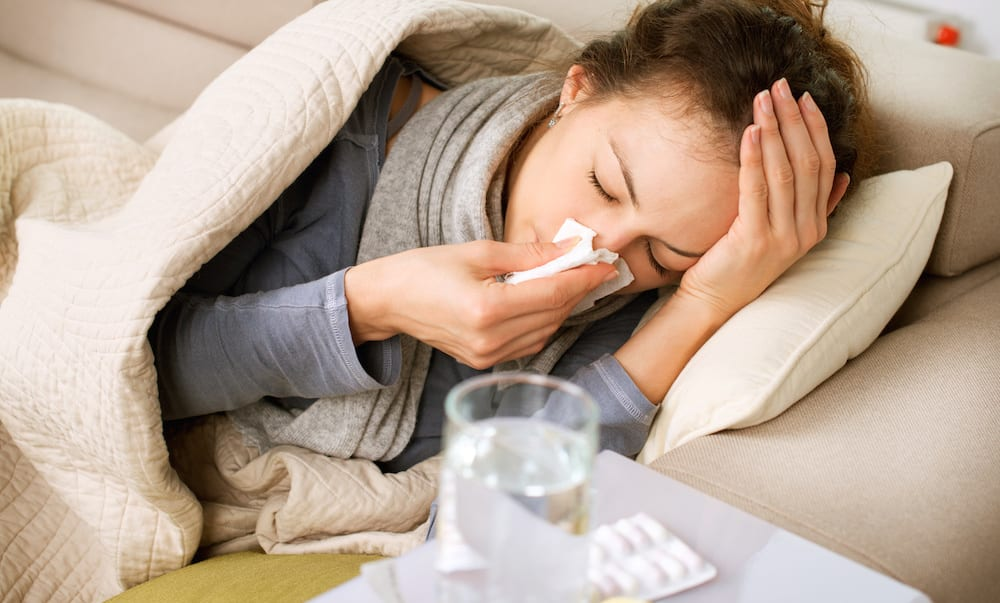 Sick Woman. Flu. Woman Caught Cold. Sneezing into Tissue