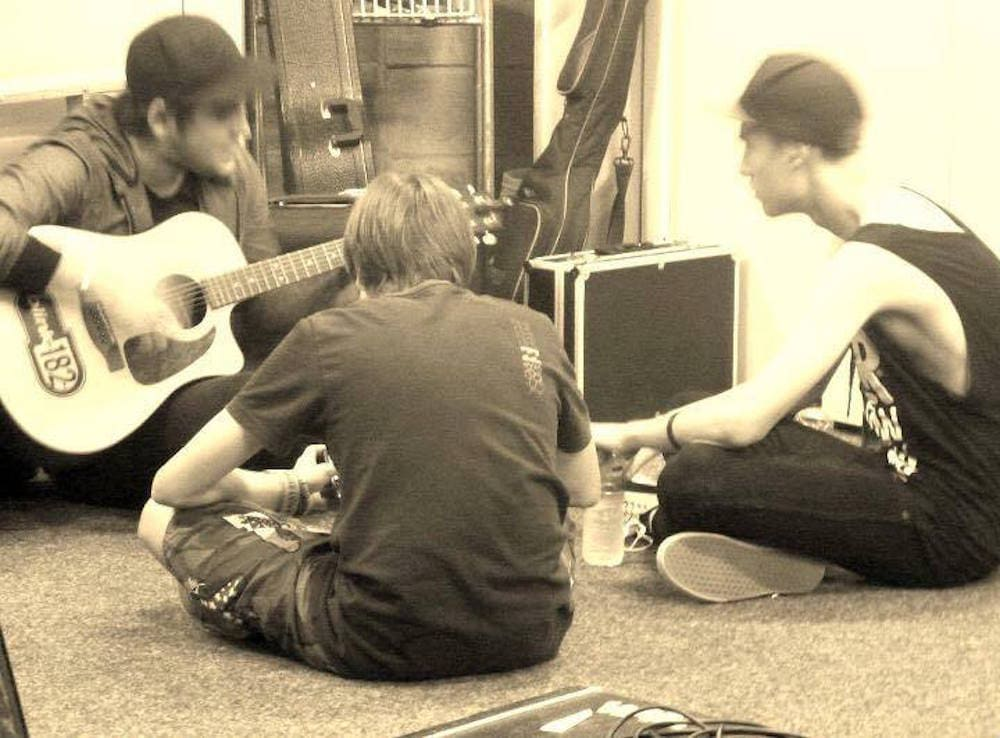 Sepia image of a band sitting on floor backstage at Tweed Battle of the Bands