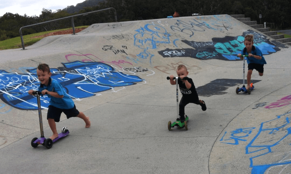 three young boys riding scooters Tweed skate parks