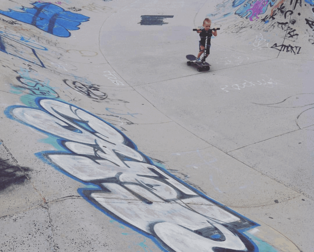 young boy riding scooter at cabarita skate park